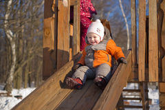 Adorable baby sliding from wooden slide in park Royalty Free Stock Image