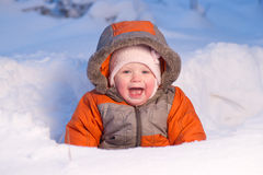 Adorable baby smile and digging hideout in snow Royalty Free Stock Photos