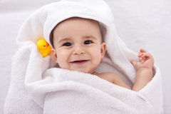 Adorable baby smiling wrapped in white towel with yellow duck Stock Photo