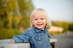 Adorable baby stay near bench leaning in park Royalty Free Stock Image