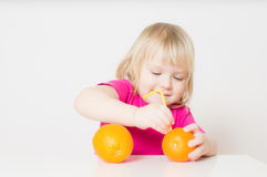 Adorable baby suck juice from orange with straw Stock Photography
