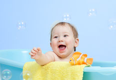 Adorable baby taking bath in blue tub Stock Photos