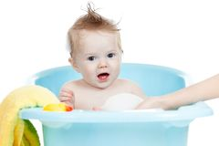 Adorable baby taking bath in blue tub Stock Images