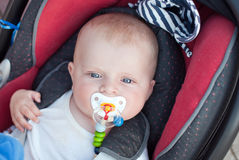 Adorable baby toddler in safety car seat. Adorable baby boy with blue eyes in safety car seat Royalty Free Stock Image