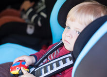 Adorable baby toddler in safety car seat. Adorable baby boy with blue eyes in safety car seat Stock Images