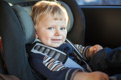 Adorable baby toddler in safety car seat. Adorable baby boy with blue eyes in safety car seat Royalty Free Stock Photos