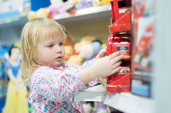 Adorable baby with toys on shelves in mall Royalty Free Stock Images