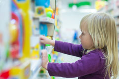 Adorable baby with toys on shelves in mall Stock Photo