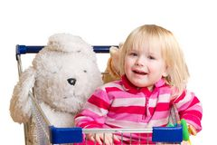 Adorable baby with toys in shop cart Stock Photos
