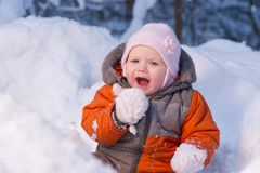 Adorable baby try to eat cold snow Royalty Free Stock Photo
