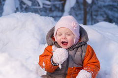 Adorable baby try to eat cold snow Royalty Free Stock Photos