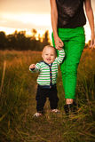Adorable baby walking around with mother. Very cute baby boy smiling and having fun with his mother outside, baby making first steps Stock Photography