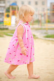 Adorable baby walking barefoot on playground Stock Images