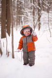 Adorable baby walking in snow forest Stock Photo