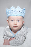 Adorable Baby Wearing Blue Knit Crown. Baby with blue eyes lying on his stomach wearing a light blue knit crown hat playing king Stock Photography
