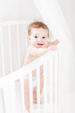 Adorable baby wearing a diaper standing in a white round crib Stock Image