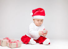 Adorable baby wearing a Santa hat opening Christmas presents Stock Photos