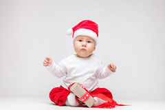 Adorable baby wearing a Santa hat opening Christmas presents Stock Image