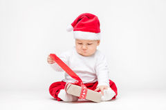 Adorable baby wearing a Santa hat opening Christmas presents Stock Images
