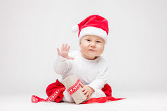 Adorable baby wearing a Santa hat opening Christmas presents Royalty Free Stock Photos