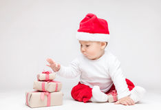 Adorable baby wearing a Santa hat opening Christmas presents Stock Photography