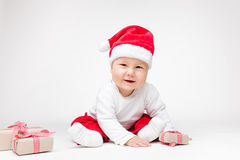 Adorable baby wearing a Santa hat opening Christmas presents Stock Photo