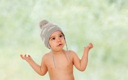 Adorable baby with wool cap asking somenthing. With green background Stock Photo