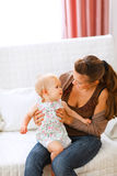 Adorable baby and young mom playing on couch Stock Image