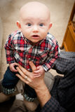 Adorable Bald Baby Boy With Big Blue Eyes. Baby with big blue eyes wide open looking upward wearing a plaid shirt and jeans Royalty Free Stock Photo