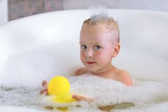 Adorable bath baby boy with soap suds on hair play with colorful toy yellow duck. Hygiene and care for young children.  stock photo