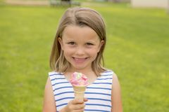 Adorable and beautiful blond young girl 6 or 7 years old eating delicious ice cream smiling happy on green grass field ba stock image