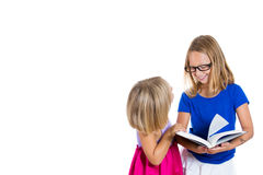 Adorable, beautiful children, sisters with glasses sharing and reading a book Stock Image