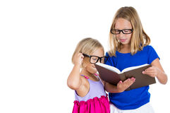 Adorable, beautiful children, sisters with glasses sharing and reading a book Stock Photos