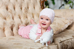 Adorable big-eyed little girl in a pink jumpsuit smiles and lies. On the couch in the interiors of the Studio, holding in her hands a toy sheep stock photo