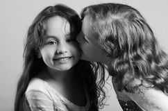 Adorable big sister kissing sibling on cheek, both wearing matcing blue dresses posing together happily, studio Stock Photography