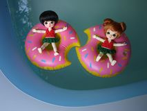Adorable BJD Ball Joint Doll branded LATI in swimming suit. They`re ready to play water with colorful pool floats. They`re repainted version royalty free stock photos