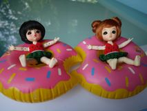 Adorable BJD Ball Joint Doll branded LATI in swimming suit. They`re ready to play water with colorful pool floats. They`re repainted version royalty free stock images
