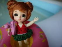 Adorable BJD Ball Joint Doll branded LATI in swimming suit. They`re ready to play water with colorful pool floats. They`re repainted version stock photos