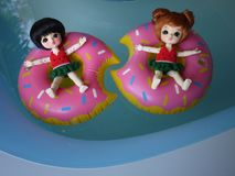 Adorable BJD Ball Joint Doll branded LATI in swimming suit. They`re ready to play water with colorful pool floats. They`re repainted version royalty free stock image