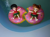 Adorable BJD Ball Joint Doll branded LATI in swimming suit. They`re ready to play water with colorful pool floats. They`re repainted version stock photo