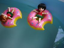 Adorable BJD Ball Joint Doll branded LATI in swimming suit. They`re ready to play water with colorful pool floats. They`re repainted version royalty free stock photography