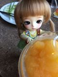 An adorable BJD ball joint doll) and orange juice stock photo
