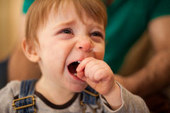 Adorable blond baby crying at home Royalty Free Stock Image
