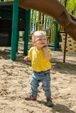 Adorable blond caucasian toddler playing on sand box royalty free stock image