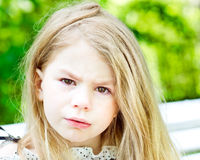 Adorable blond crying little girl with tears on her cheeks. Portrait of an adorable blond crying little girl with tears on her cheeks Royalty Free Stock Images