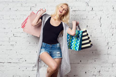 Adorable blond girl against the wall with shopping. Bags with new purchases laughing out loud wearing summer clothes Stock Image