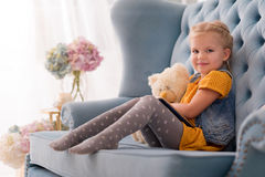 Adorable blond girl holding her favourite toy. Playing with toys. Good looking joyful blond girl sitting on the couch and smiling while holding her favourite Stock Photos