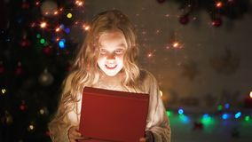 Adorable blond girl opening gift box, magic Christmas atmosphere, glowing effect. Stock footage stock video footage