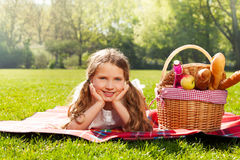 Adorable blond girl on the picnic in spring park. Portrait of adorable 10 years old girl laying on picnic blanket next to basket full of beverages and snacks in Stock Image