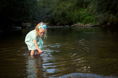 Adorable blond girl playing in river, exploration concept Royalty Free Stock Photography